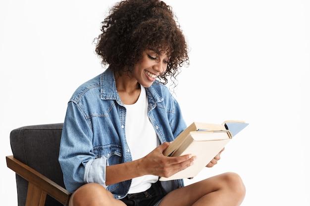 Aantrekkelijke jonge vrouw met denim zittend in een stoel geïsoleerd over een witte muur, papieren boek lezend