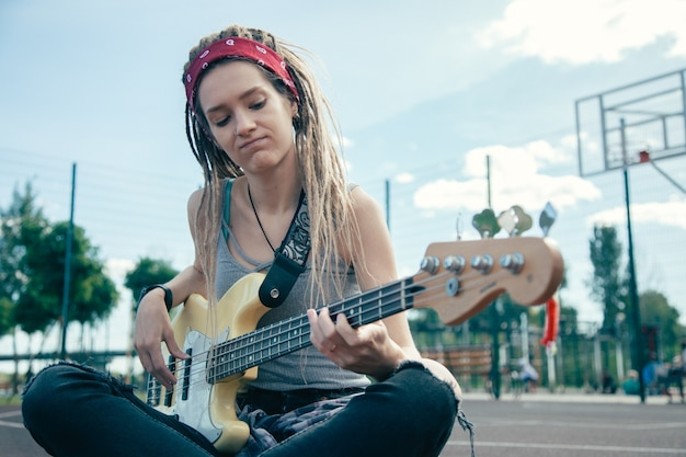 Aantrekkelijke jonge vrouw met dreadlock zittend op het sportveld en geconcentreerd kijken tijdens het spelen van de gitaar