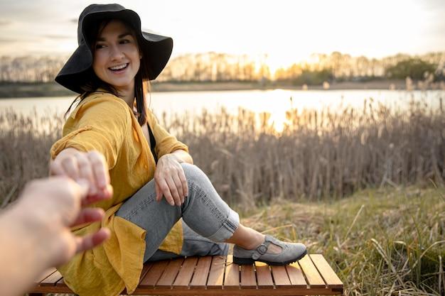 Aantrekkelijke jonge vrouw met een glimlach op haar gezicht houdt de hand van de fotograaf vast bij het meer bij zonsondergang