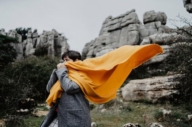 Aantrekkelijke jonge vrouw met een jas en een gele sjaal in de buurt van hoge rotswanden