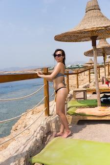 Aantrekkelijke jonge vrouw met een zonnebril die voor een houten hek staat met touwinzetstukken en zee met koralen en riffen tegen de lucht