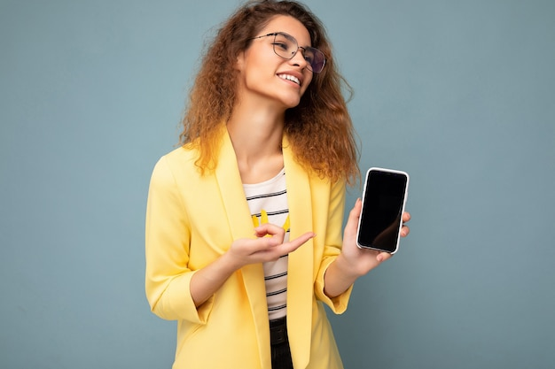 Aantrekkelijke jonge vrouw met krullend donkerblond haar met een gele jas en een optische bril die op de achtergrond wordt geïsoleerd en mobiele telefoon toont met lege ruimte voor uitsnijding.