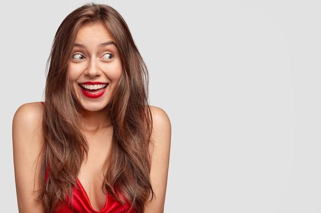 Aantrekkelijke jonge vrouw met lang donker steil haar, heeft een gelukkige uitdrukking, rode lippen, nonchalant gekleed, staat tegen een witte muur