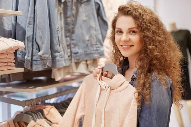 Aantrekkelijke jonge vrouw met positieve expressie, houdt trui op hangers