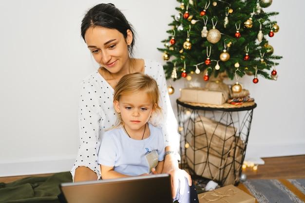 Aantrekkelijke jonge vrouw met schattige dochtertje online chatten feliciteren met familie of vrienden met digitale tablet videochat met ouders en grootouders op kerstmis