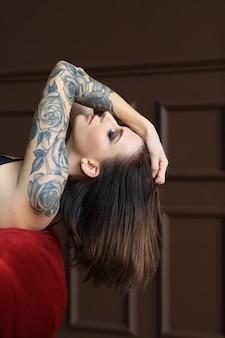 Aantrekkelijke jonge vrouw met tattoo poseren