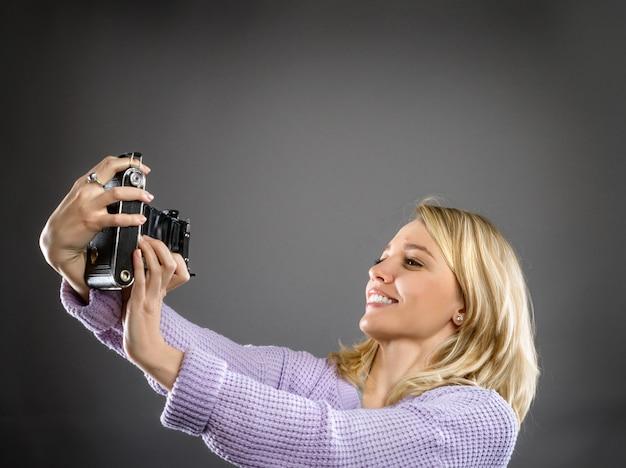 Aantrekkelijke jonge vrouw met vintage draagbare camera