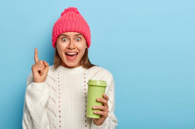 Aantrekkelijke jonge vrouw met vrolijke gezichtsuitdrukking, wijsvinger wijst boven, toont coole promotie, houdt groene afhaalmaaltijden kopje koffie, draagt winter outfit