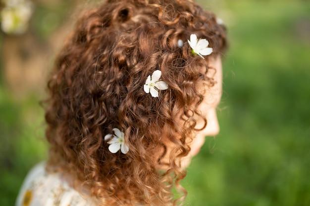 Aantrekkelijke jonge vrouw met witte bloemen geweven in haar krullend haar. lente mode concept