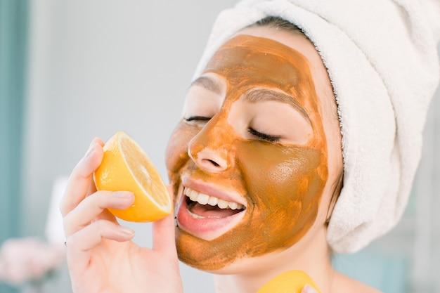 Aantrekkelijke jonge vrouw met witte handdoek op het hoofd en met modder bruin gezichtsmasker bijt een citroen en glimlacht. schoonheid, spa, huid en lichaamsverzorging.