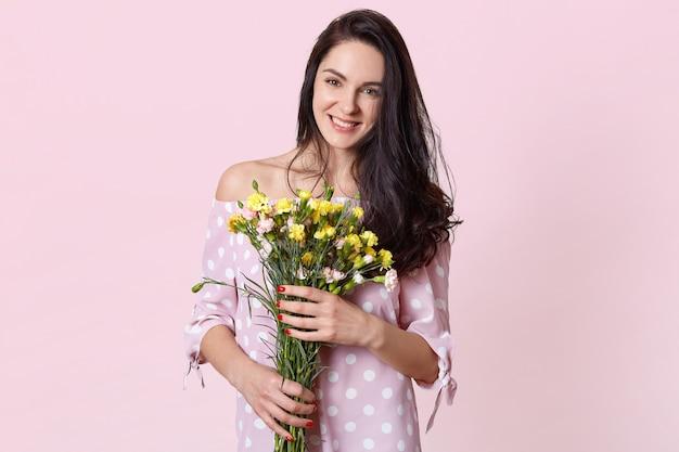 Aantrekkelijke jonge vrouw met zwart lang golvend haar, houdt bloemen vast, gekleed in een jurk met stippen, heeft een lentestemming, poseert op lichtroze, heeft een romantische date met een vriendje. 8 maart concept