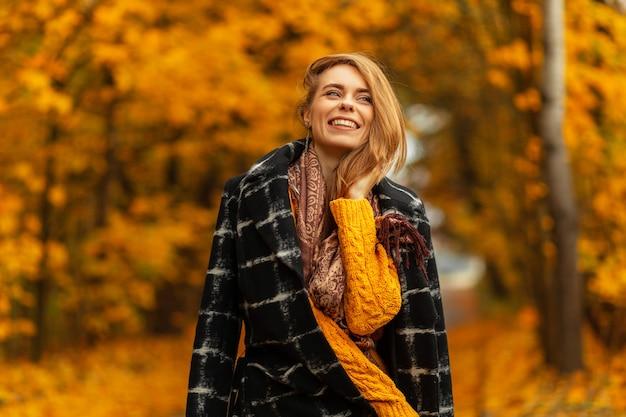 Aantrekkelijke jonge vrouw model in stijlvolle strohoed in elegant gestreept shirt in broek staat in de buurt van metalen reling op straat op zomerdag. mooi meisje in mode kleding poseert in de buurt van zwart gebouw buitenshuis