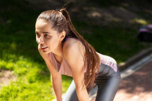 Aantrekkelijke jonge vrouw neemt een pauze na het sporten