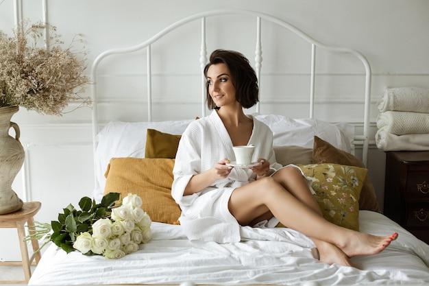 Aantrekkelijke jonge vrouw op blote voeten in een witte badjas, zittend met een kopje koffie op het bed. een boeket rozen naast haar