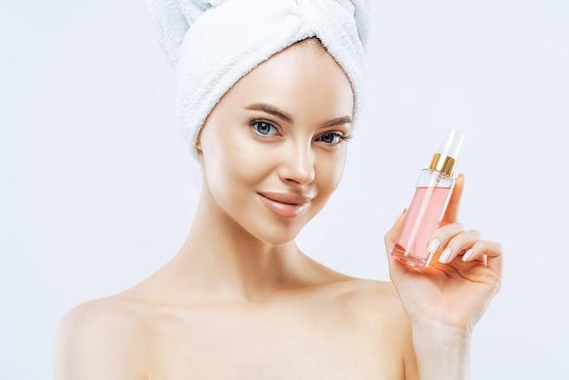 Aantrekkelijke jonge vrouw past parfum toe, geniet van een aangename geur, staat met blote schouders, heeft natuurlijke make-up, een gezonde huid, een handdoek om het hoofd gewikkeld na het nemen van een douche. geweldig aroma, probeer dit.
