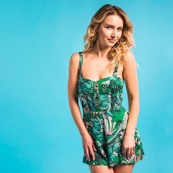 Aantrekkelijke jonge vrouw poseren in bloemrijke jurk