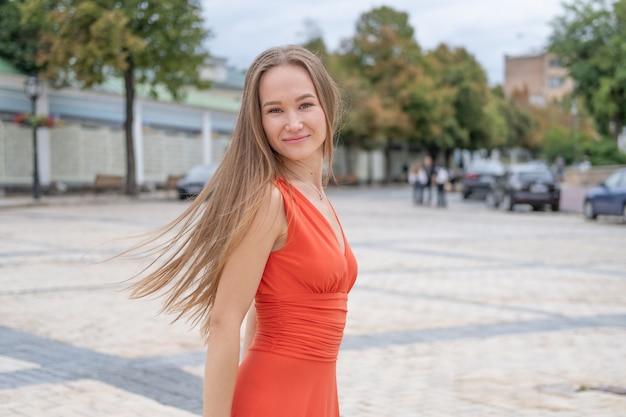 Aantrekkelijke jonge vrouw poseren met rode jurk in de straat