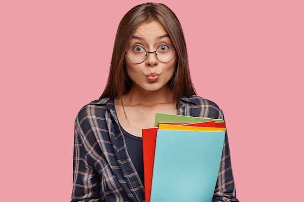 Aantrekkelijke jonge vrouw poseren tegen de roze muur met bril