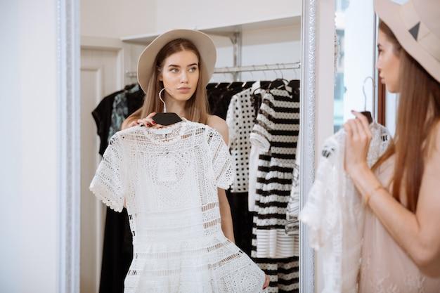 Aantrekkelijke jonge vrouw probeert op jurk voor spiegel in kledingwinkel