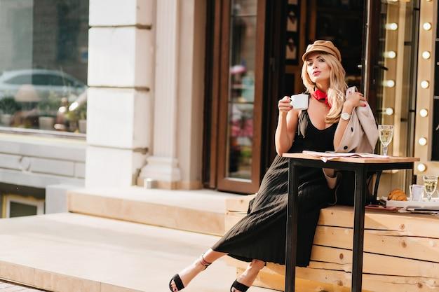 Aantrekkelijke jonge vrouw rusten na het werk in favoriete café en genieten van koffiesmaak. outdoor portret van blond meisje in stijlvolle outfit ontspannen in het weekend.