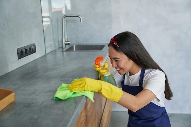 Aantrekkelijke jonge vrouw, schoonmaakster die lacht terwijl ze de keuken schoonmaakt en de oppervlakken besproeit met wasmiddel uit een spuitfles. huishoudelijk werk en huishouden, schoonmaakserviceconcept