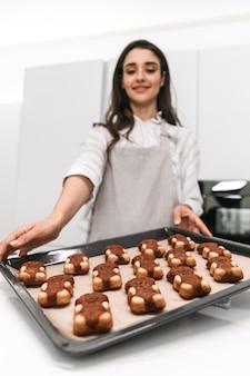 Aantrekkelijke jonge vrouw smakelijke koekjes koken op een dienblad terwijl je in de keuken staat
