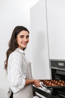 Aantrekkelijke jonge vrouw smakelijke koekjes koken op een dienblad terwijl ze in de keuken staan, uit een oven halen