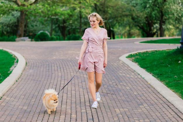 Aantrekkelijke jonge vrouw spitz hond buiten lopen