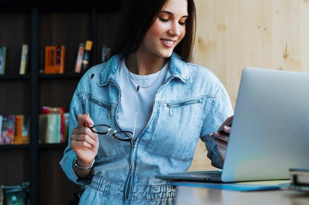 Aantrekkelijke jonge vrouw staat in de buurt van het raam, houdt smartphone in haar hand, bril voor visie en werkt op laptop.
