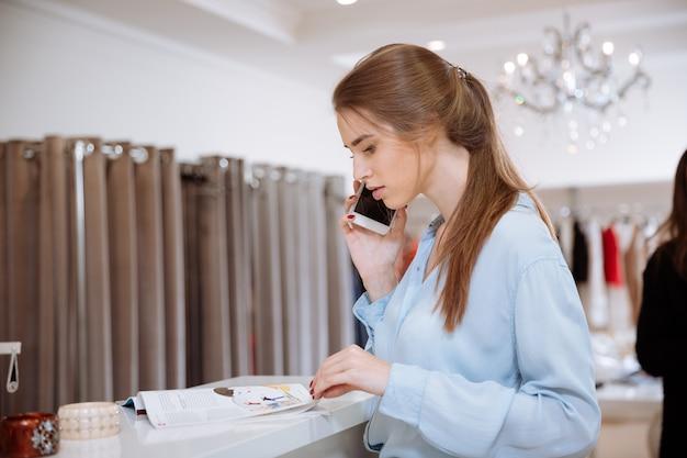 Aantrekkelijke jonge vrouw tijdschrift lezen en praten op mobiele telefoon in kledingwinkel