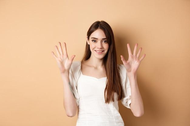 Aantrekkelijke jonge vrouw toont vingers nummer tien, glimlachend en kijkend zelfverzekerd, staande op beige achtergrond.