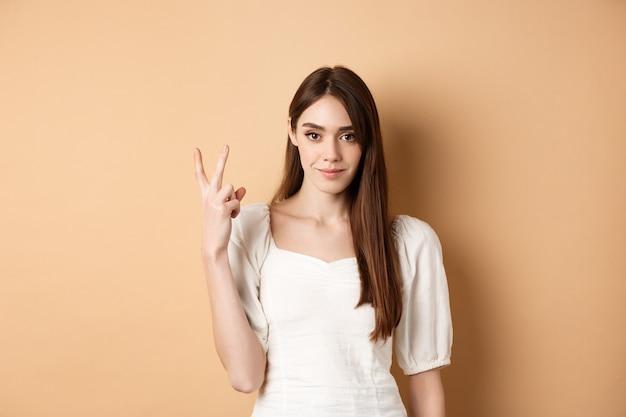 Aantrekkelijke jonge vrouw toont vingers nummer twee, glimlachend en kijkend zelfverzekerd, staande op beige achtergrond.