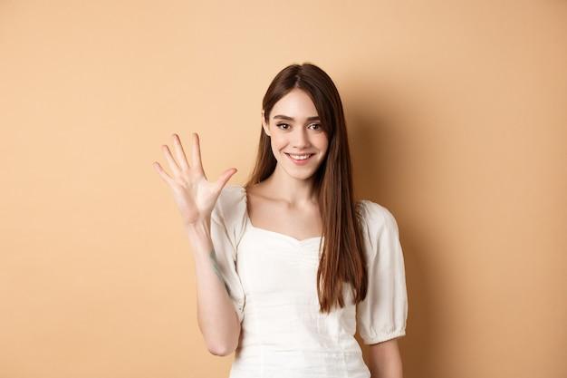 Aantrekkelijke jonge vrouw toont vingers nummer vijf, glimlachend en kijkend zelfverzekerd, staande op beige achtergrond.