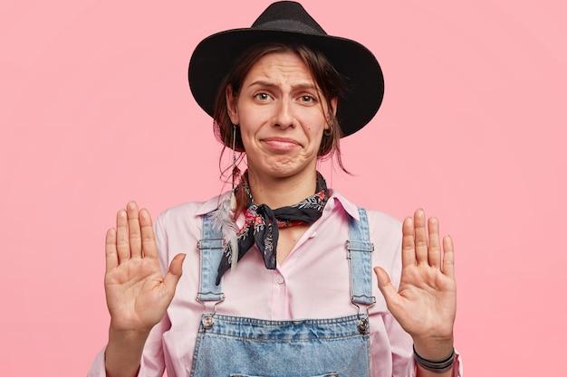 Aantrekkelijke jonge vrouw werknemer in vrijetijdskleding en hoed, toont palmen op camera, fronst gezicht, vraagt om vrede, staat tegen roze muur