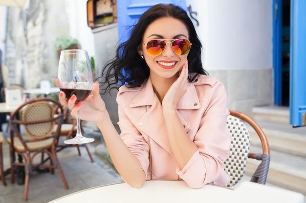 Aantrekkelijke jonge vrouw wijn drinken op zomervakantie zitten in stad straat café in coole outfit