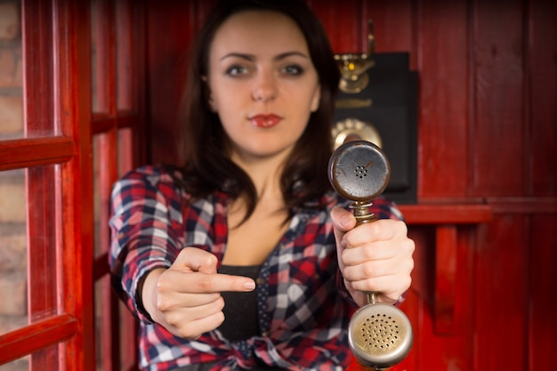 Aantrekkelijke jonge vrouw wijst naar een vintage telefoonhoorn terwijl ze deze naar de kijker uitstrekt in een behulpzaam gebaar dat een inkomende oproep aangeeft