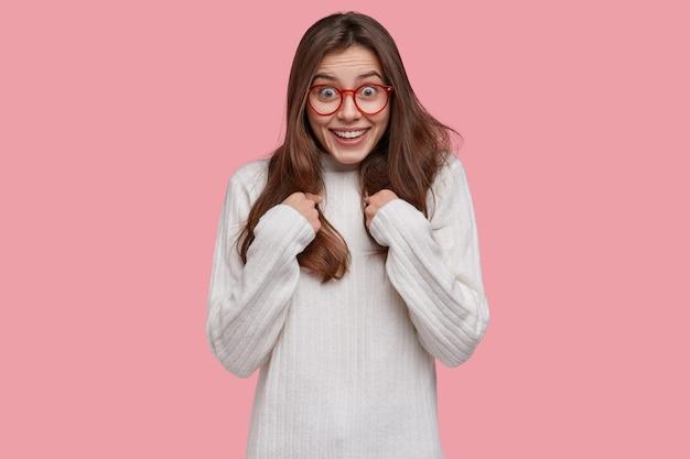 Aantrekkelijke jonge vrouw wijst naar zichzelf, vraagt iets, gekleed in casual trui