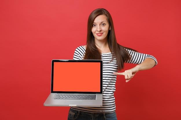 Aantrekkelijke jonge vrouw wijzende wijsvinger op laptop pc-computer met leeg zwart leeg scherm geïsoleerd op heldere rode muur achtergrond. mensen oprechte emoties, lifestyle concept. bespotten kopie ruimte.