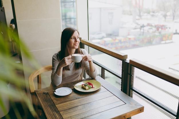 Aantrekkelijke jonge vrouw zit alleen in de buurt van groot raam in coffeeshop aan tafel met kopje cappuccino, cake, ontspannen in restaurant tijdens vrije tijd. jonge vrouw met rust in café. levensstijlconcept.