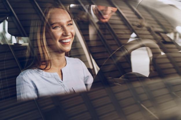 Aantrekkelijke jonge vrouw zit in nieuwe auto in showroom