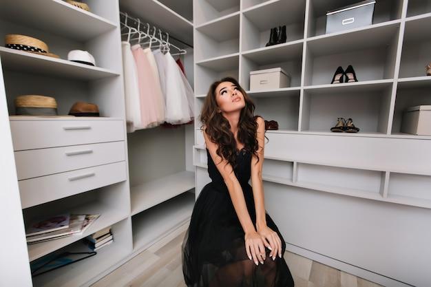 Aantrekkelijke jonge vrouw zitten in de kleedkamer, denken wat te dragen, moeilijk keuze maken, beslissen, dromen over nieuwe kleren. dame heeft lang krullend haar, zwarte mooie jurk, elegante witte manicure.