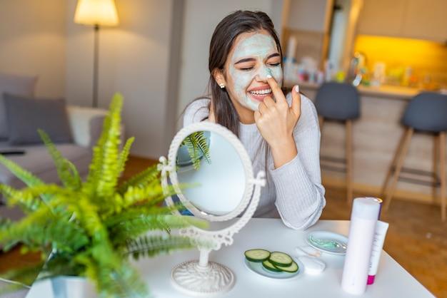 Aantrekkelijke jonge vrouw zitten met een gezichtsmasker op haar huid