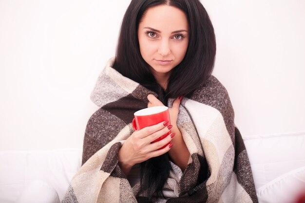 Aantrekkelijke jonge vrouw zitten met een kopje koffie in een wit bed