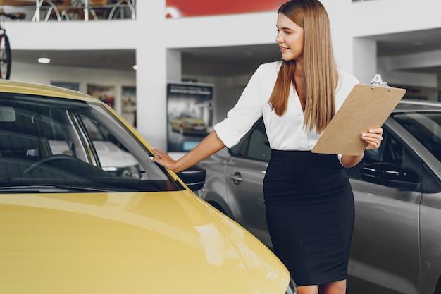 Aantrekkelijke jonge vrouwelijke autodealer die zich in toonzaal bevindt