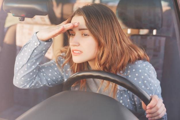 Aantrekkelijke jonge vrouwelijke bestuurder kijkt aandachtig naar de voorruit in de verte en probeert iets op de voorgrond te zien