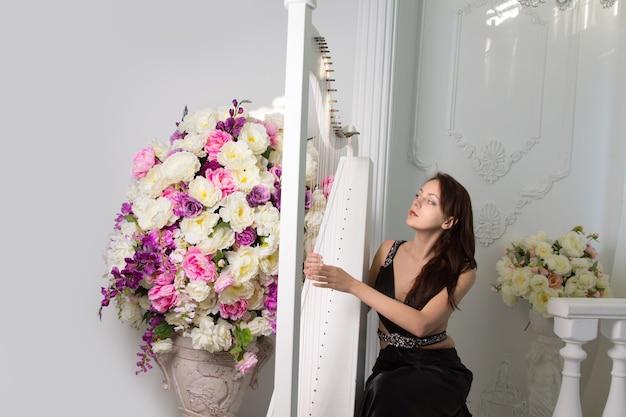 Aantrekkelijke jonge vrouwelijke klassieke muzikant die de harp speelt tijdens een concert of recital terwijl ze de snaren plukt voor een groot kleurrijk bloemstuk