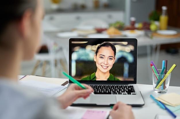 Aantrekkelijke jonge vrouwelijke leraar lacht naar haar studenten, met behulp van videochat-app tijdens online les. thuisonderwijs tijdens quarantaine. focus op laptopscherm