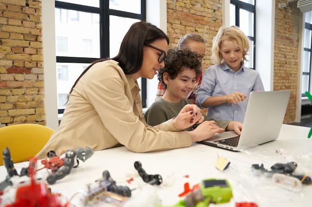 Aantrekkelijke jonge vrouwelijke leraar met een bril die wetenschappelijke robotica-video laat zien aan nieuwsgierige kinderen die gebruik maken van