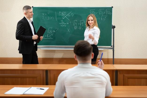 Aantrekkelijke jonge vrouwelijke student in een kort rokje antwoordt een mannelijke leraar