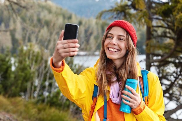 Aantrekkelijke jonge vrouwelijke toerist maakt selfie portret op slimme telefoon, warme koffie of thee drinkt uit thermoskan